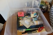 3 books of scrapbooking paper, wash tape, adhesive ribbon, 1 sticker sheet, Project Life corner rounder, post it notes, scotch tape adhesive roller, and fine point sharpie pens.